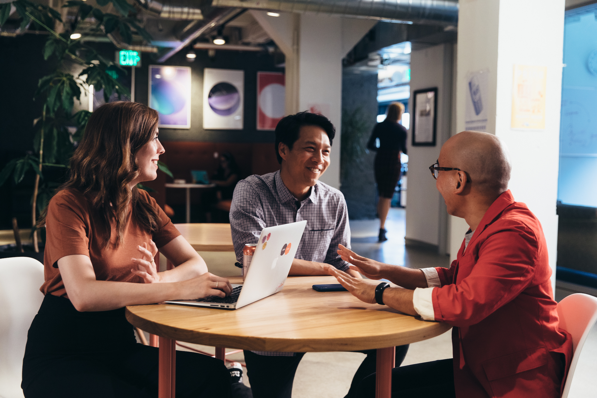 A group of Asana employees talking to each other